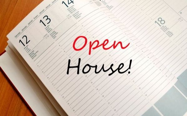 A day planner open and open house marked in it for a real estate agent
