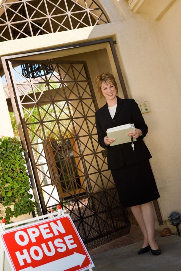 A real estate agent standing in front of a luxury home with gated door. She has a folder, keys, and an open house sign.